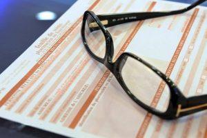 paire de lunettes sur une feuille de remboursement de la sécurité sociale
