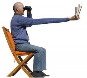 homme essayant de lire un livre avec des jumelles